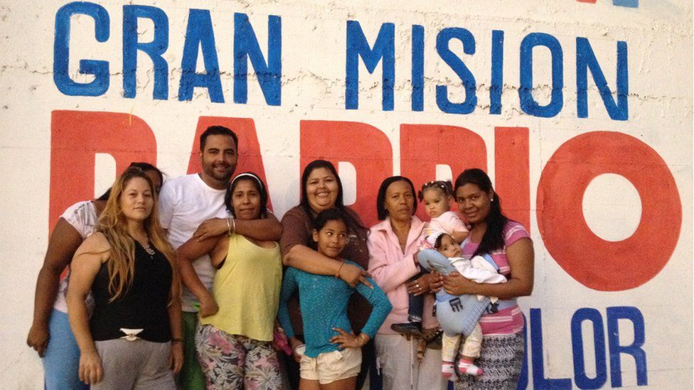 """A group of residents pose before a sign reading """"Gran Mision Barrio"""" (""""Great Neighbourhood Mission)"""