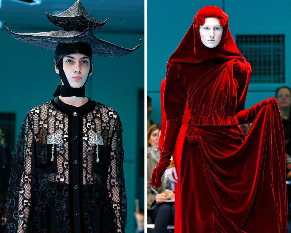 Two models on the catwalk, one wearing a black top with a black hat in the shape of tiered building, the other wearing a red velvet dress including a red headscarf