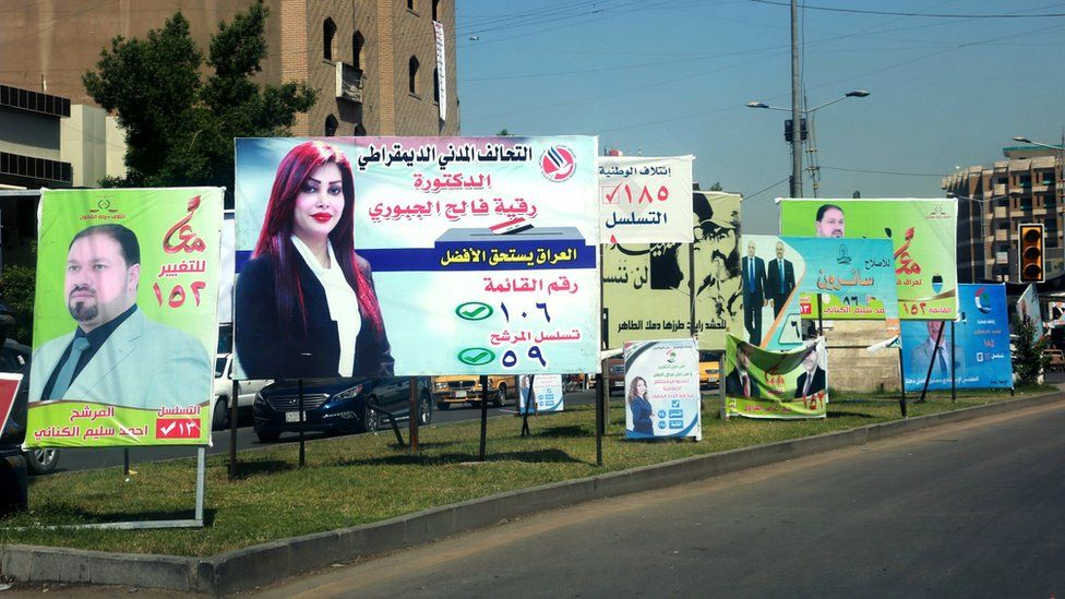 Election posters featuring men and women are seen in Baghdad, Iraq, on 19 April
