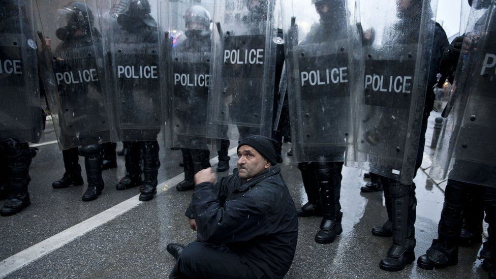A man sits in front of a cordon of policemen in riot gear during the demonstration