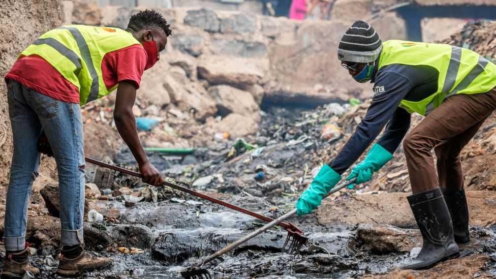 People working as part of government scheme to clear open sewers in Kibera, Kenya