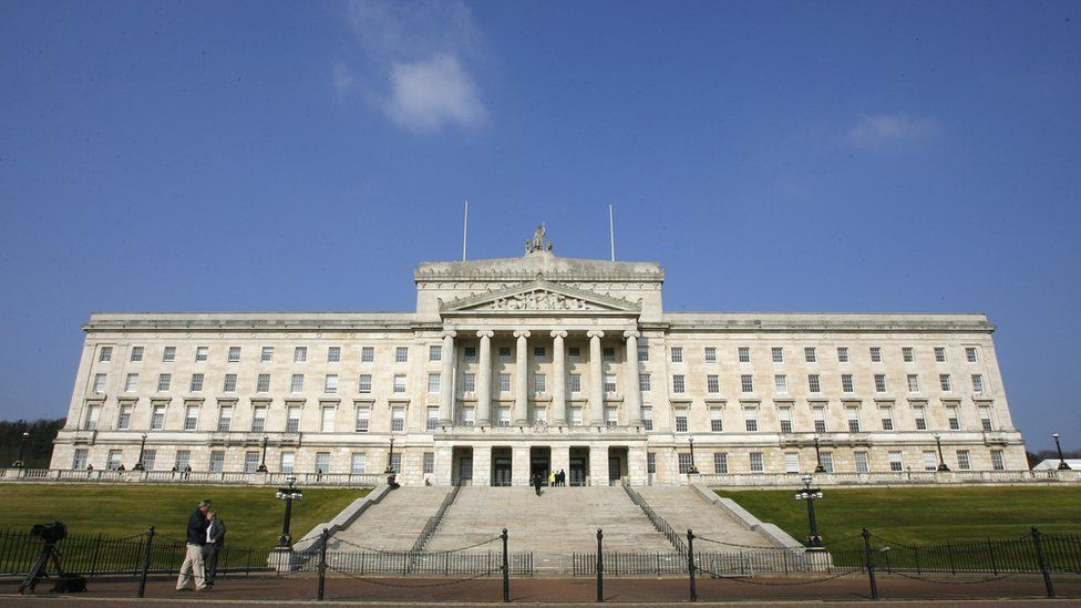 People walk past the Stormont Assembly building in Belfast