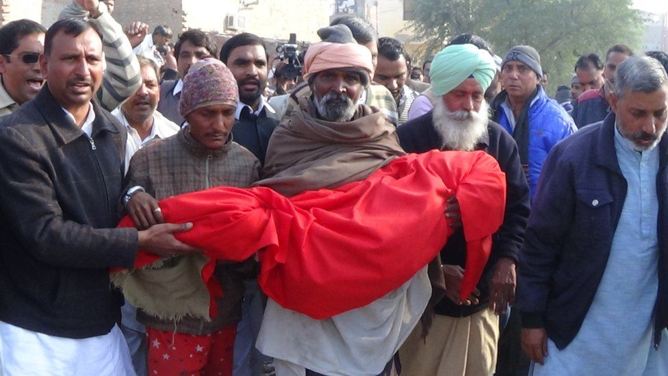 Locals carry the body of the six-year-old who was brutally raped and murdered