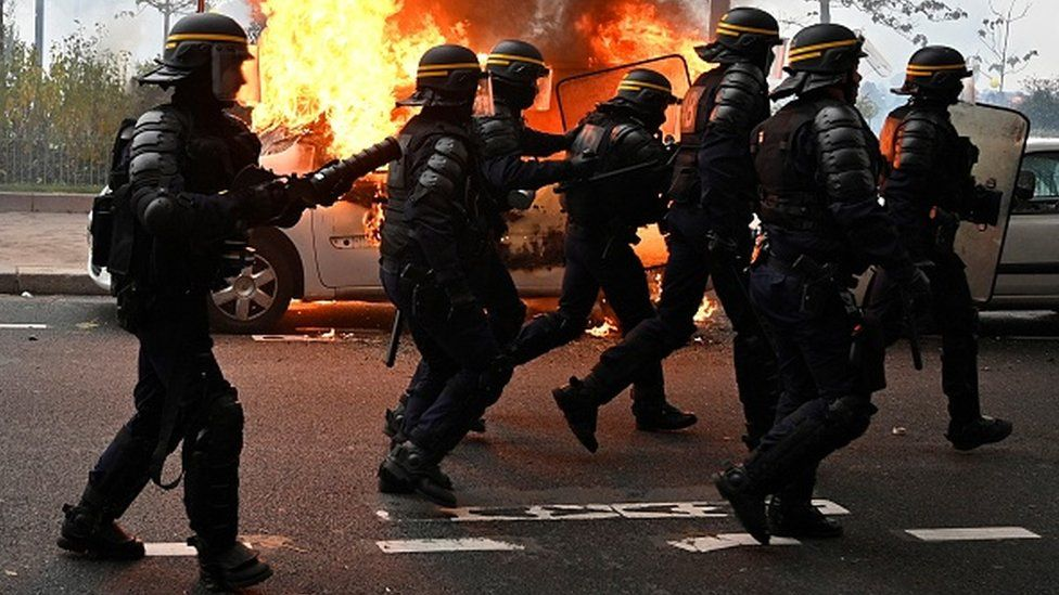 French riot police run past a vehicle set alight during yellow vests protests