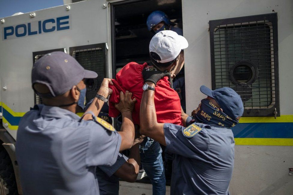 South African Police Service officers force a student member of the Economic Freedom Fighters inside a police van during a protest in Braamfontein, Johannesburg on 10 March 2021.