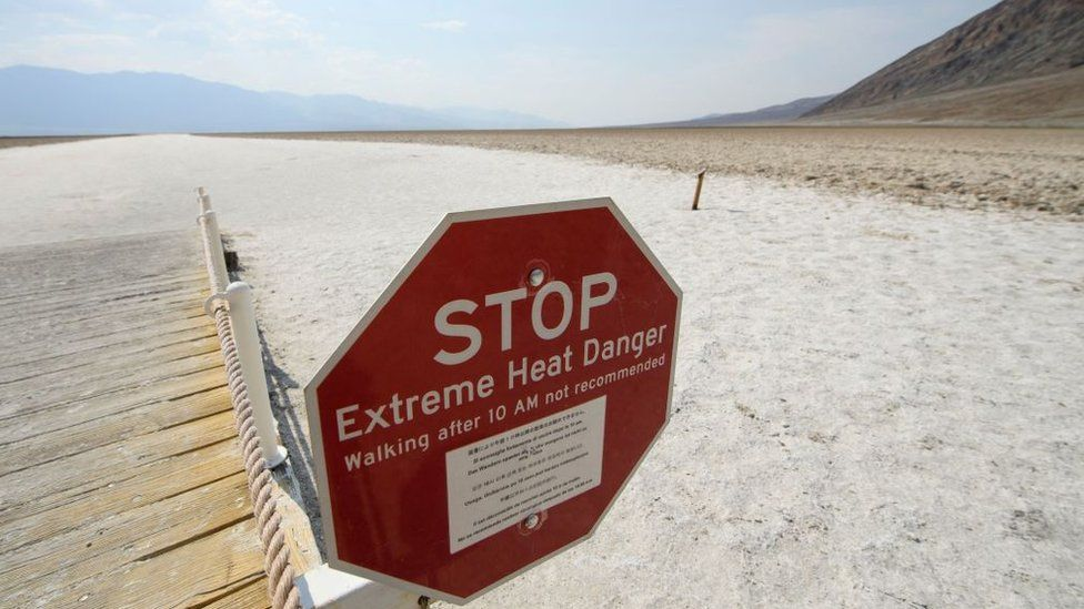 Signage warns of extreme heat danger at the salt flats of Badwater Basin inside Death Valley National Park