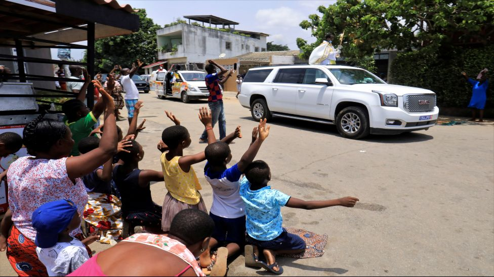Children raise their arms as Eric Norbert Abekan travels past in Abidjan, Ivory Coast - Sunday 20 March 2020