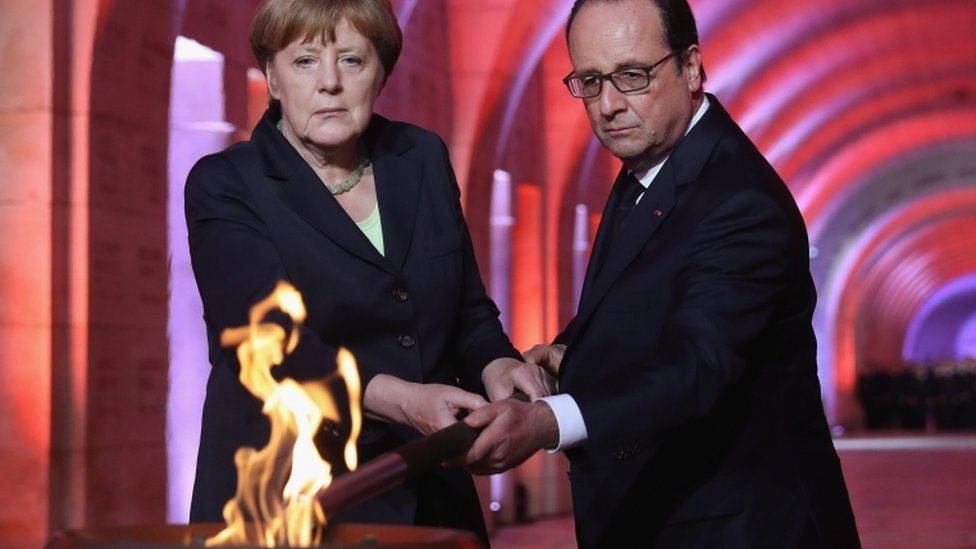 French President Francois Hollande and German Chancellor Angela Merkel light an eternal flame inside the ossuary at Douaumont in memory of the 130,000 soldiers whose remains are buried at the site
