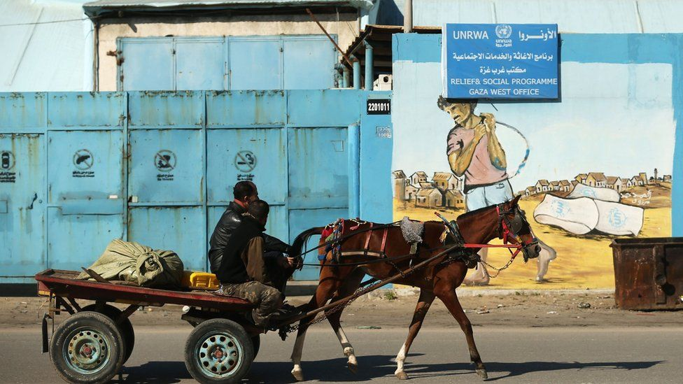 A Palestinian man rides a horse and car past an Unrwa office in Gaza City on 8 January 2018