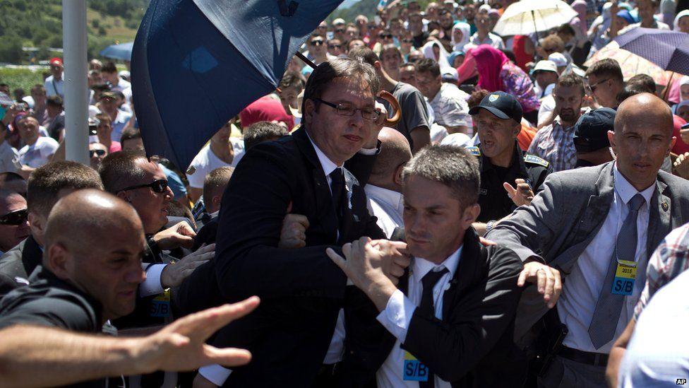 Serbian PM Aleksandar Vucic, centre, is seen during a scuffle at the Potocari memorial complex near Srebrenica