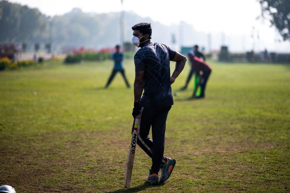 A youth (C) wearing a facemask as a preventive measure against the COVID-19 coronavirus plays cricket with his friends at a park in New Delhi on March 18, 2020.