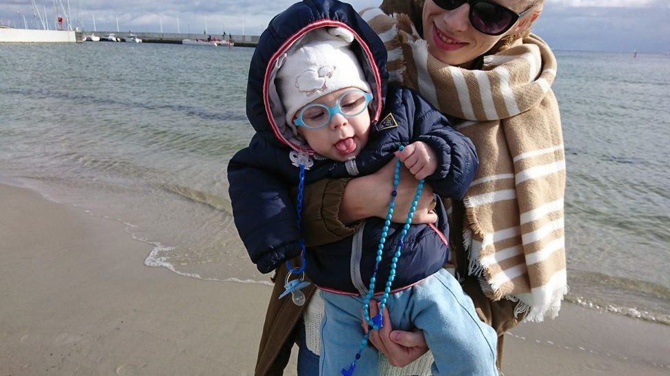 Mother with baby praying on a beach in Gdynia