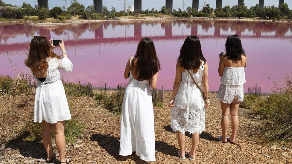 Four women dressed in white take pictures of the pink lake