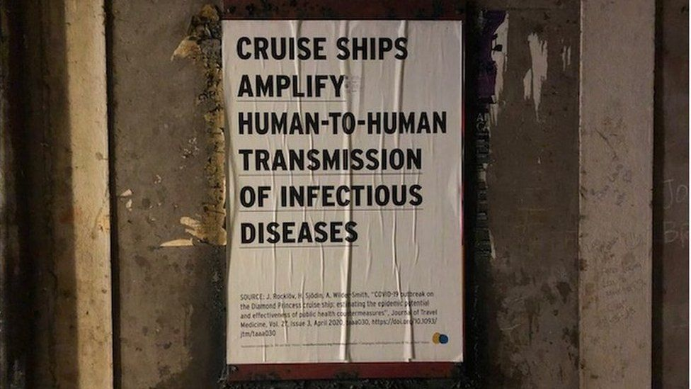 """Poster stuck to a wall saying """"cruise ships amplify transmission of infectious diseases"""""""