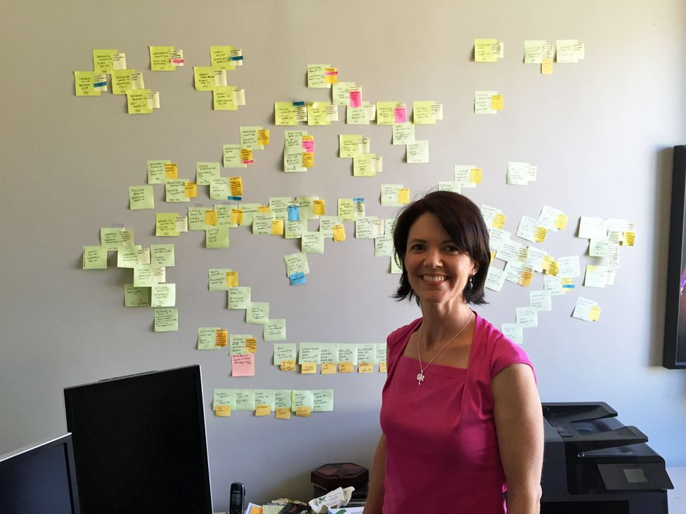 Genealogist Michelle Trostler in front of the 'wall of stickies' she assembled for the case