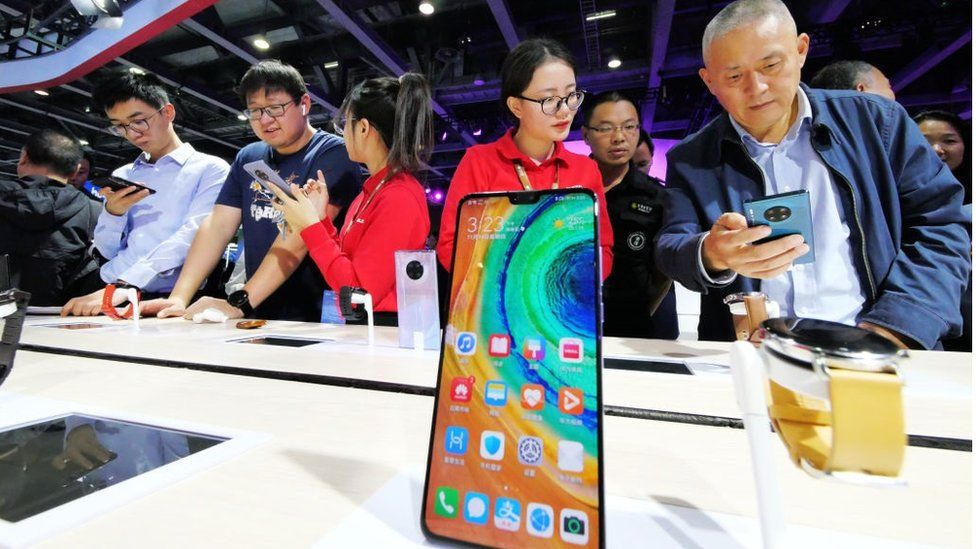 People try out 5G mobile phones at Huawei booth during China Mobile Global Partners Conference 2019 at Poly World Trade Center Expo on November 14, 2019 in Guangzhou, Guangdong Province of China.
