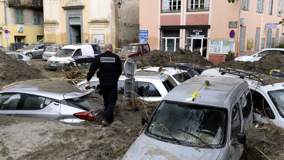 A police officer walks amongst vehicles submerged in mud in Breil-sur-Roya, south-eastern France