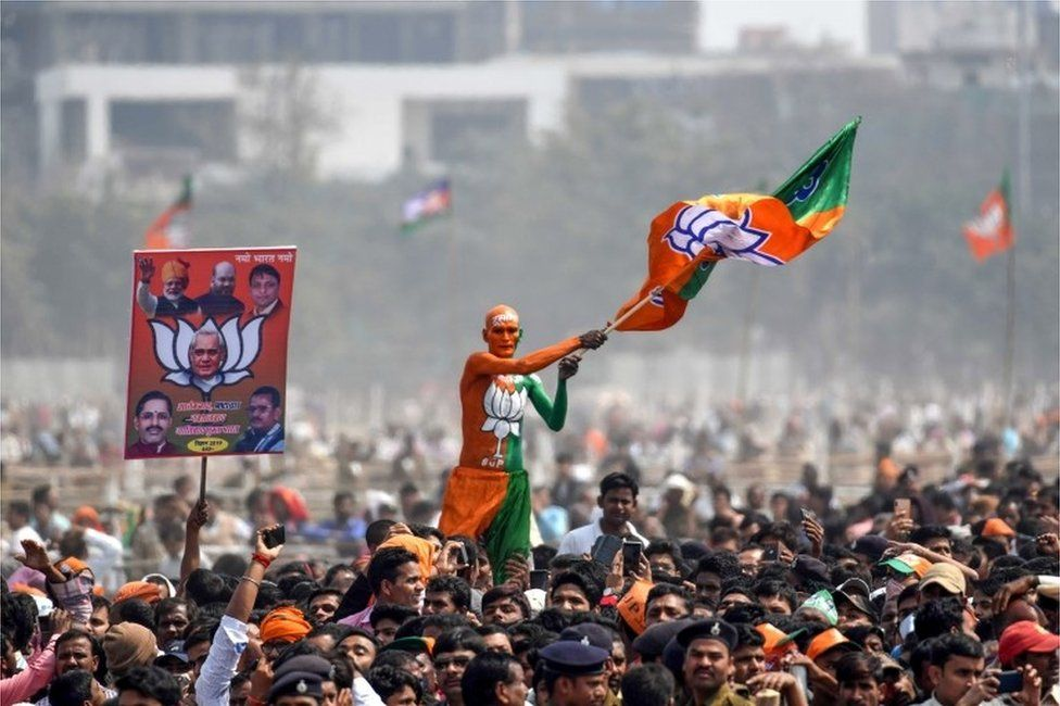 """An Indian Bharatiya Janata Party (BJP) supporter waves a flag among the crowd of other supporters listening to Prime Minister Narendra Modi during the National Democratic Alliance (NDA) """"Sankalp"""" rally in Patna in the Indian eastern state of Bihar on March 3, 2019"""