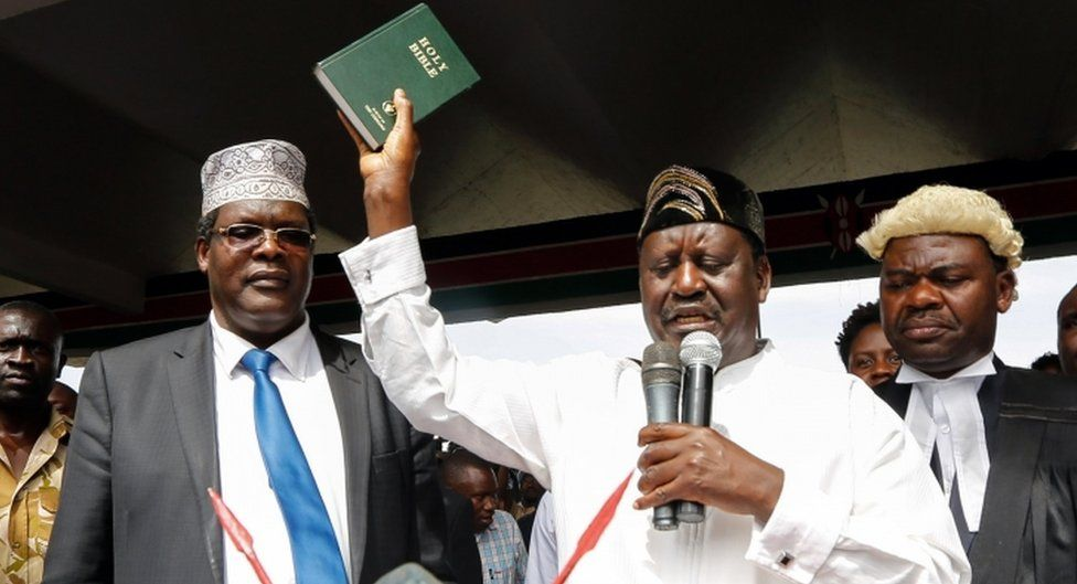 """Raila Odinga raises a bible as he """"takes an oath"""" during an unofficial """"swearing-in"""" ceremony in Nairobi on 30 January 2018."""