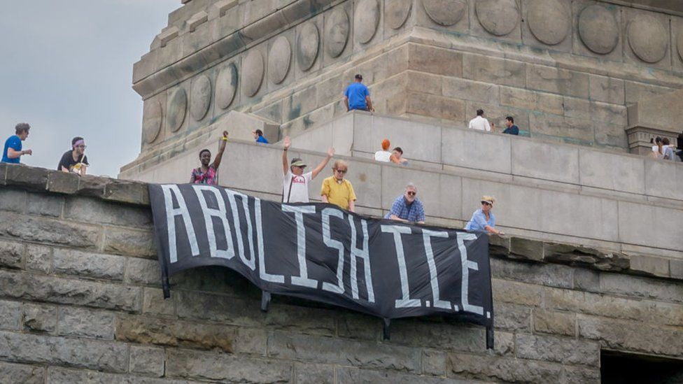 Rise and Resist unfurl a banner