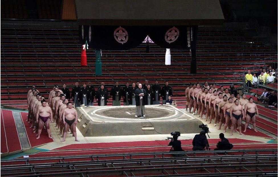 Sumo Association chairman Hakkaku (C) greets sumo wrestlers during the spring grand sumo tournament held behind closed doors due to the outbreak of the COVID-19 coronavirus, in Edion Arena Osaka in Osaka on March 8, 2020