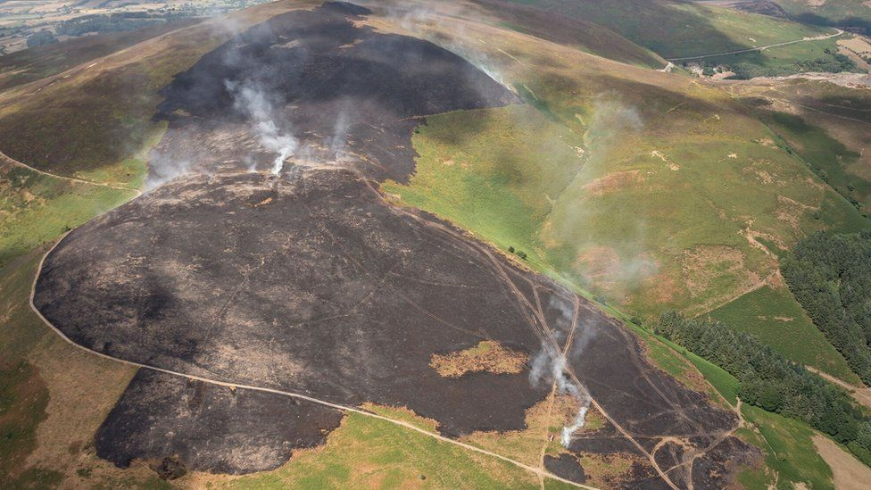 Aerial shot smouldering landscape caused by a wildfire on Llantysilio Mountain in Llangollen