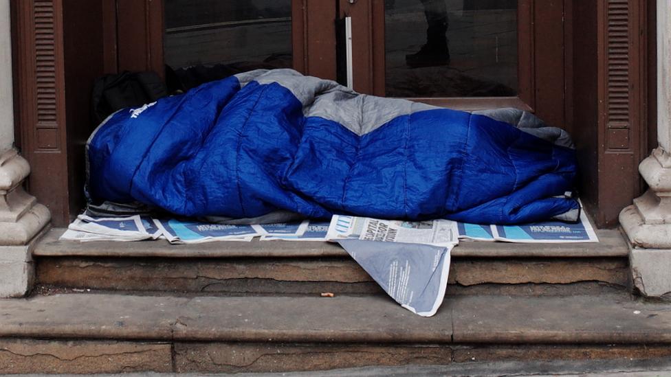 person sleeping at a door entrance