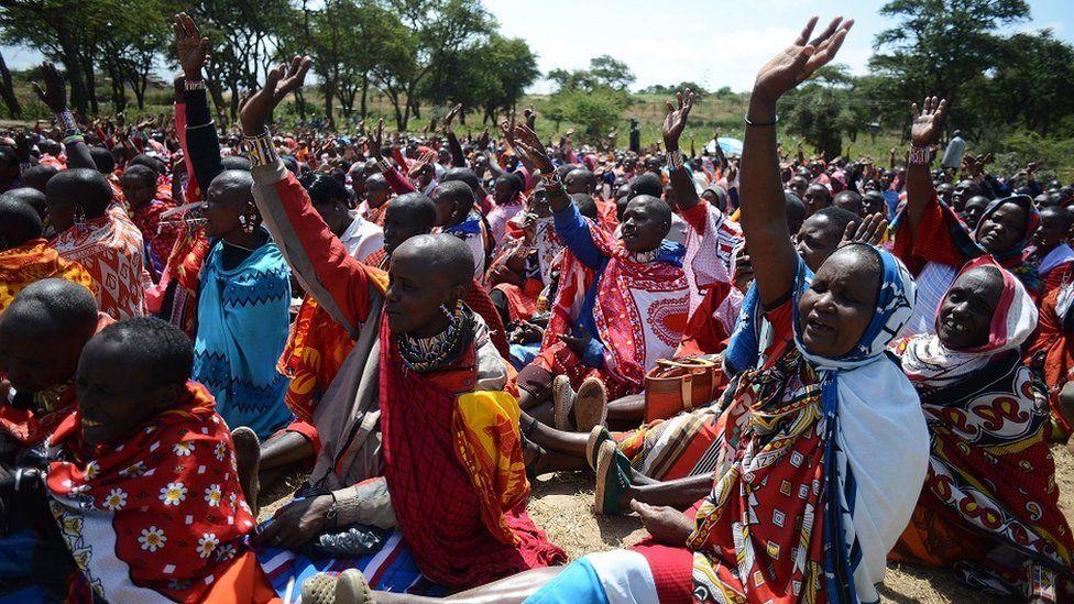 Kenyan Maasai women raise their hands as they gather during a meeting dedicated to the practice of female genital mutilation on June 12, 2014, in Enkorika, Kajiado, 75km from Nairobi.