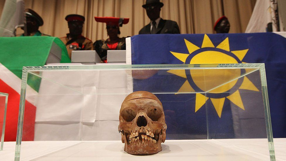 Members of a delegation from Namibia stand over 20 skulls from the Herero and Nama tribal groups at the conclusion of a ceremony at Charite hospital in Berlin, Germany to repatriate the skulls on 30 September 2011