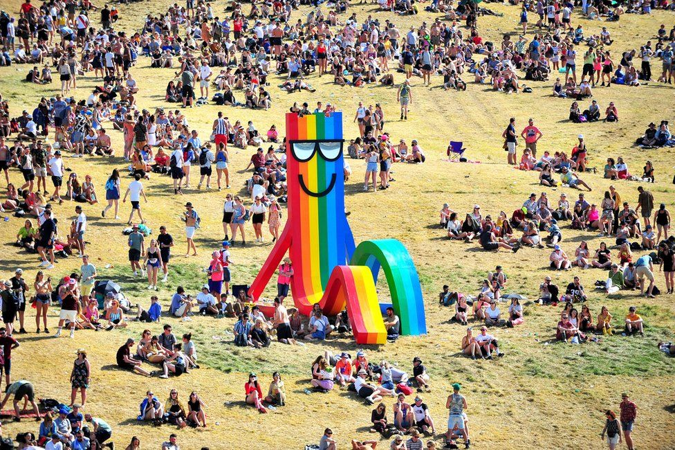 Festival-goers gather near a statue by artist Paul Insect at Glastonbury Festival