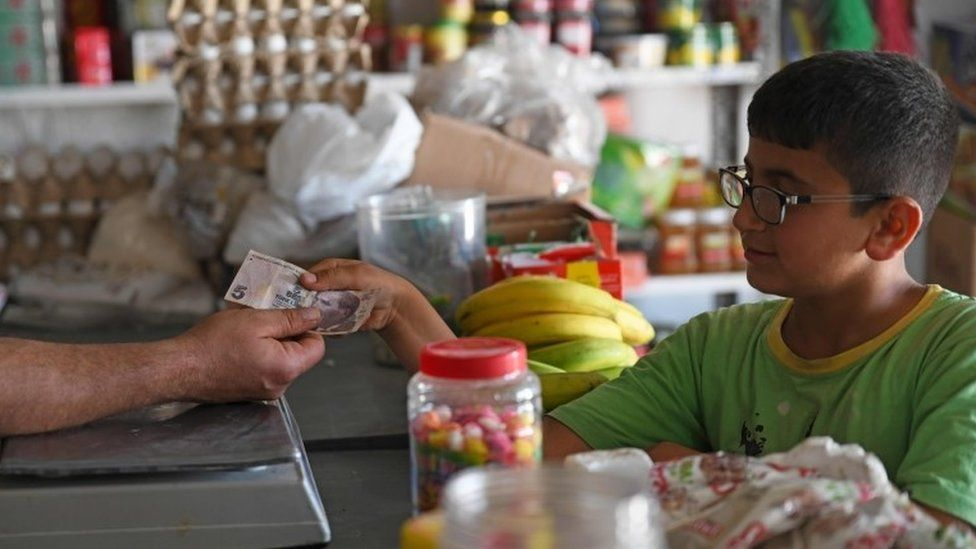 A boy uses Turkish lira to buy food at a shop in rebel-held Aleppo province, Syria (10 June 2020)