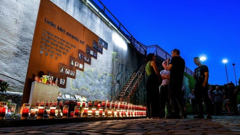 Candles are lit at the scene of the 2010 Love Parade disaster at the memorial site in Duisburg, Germany, July 2018