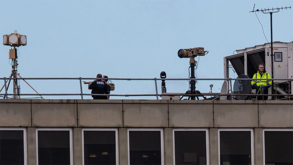 Police and security personnel on the roof of a building at Gatwick Airport on December 21