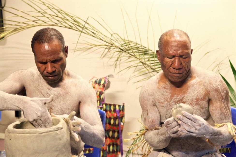 Two mud men from Papua New Guinea show visitors how to make the masks