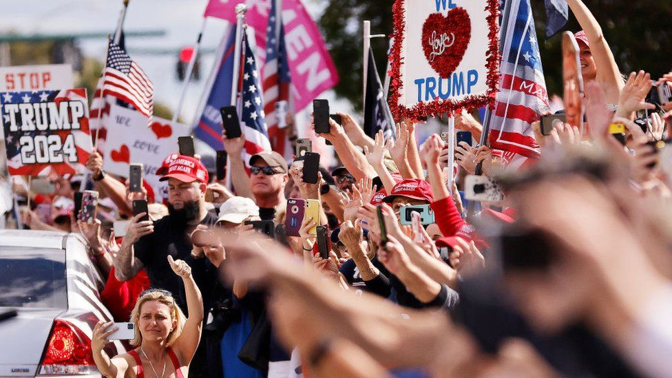 Supporters wave t Donald Trump as he returns to Florida along the route leading to his Mar-a-Lago estate on in West Palm Beach, Florida