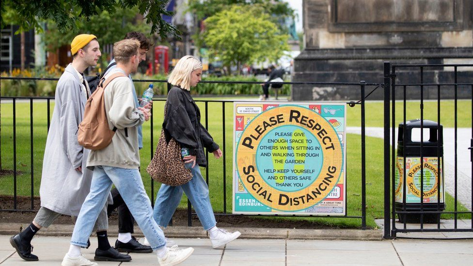 Edinburgh people walk past a sign advertising social distancing