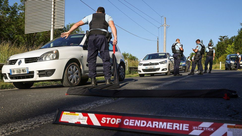 French gendarmes check vehicles during the manhunt of a heavily armed former soldier