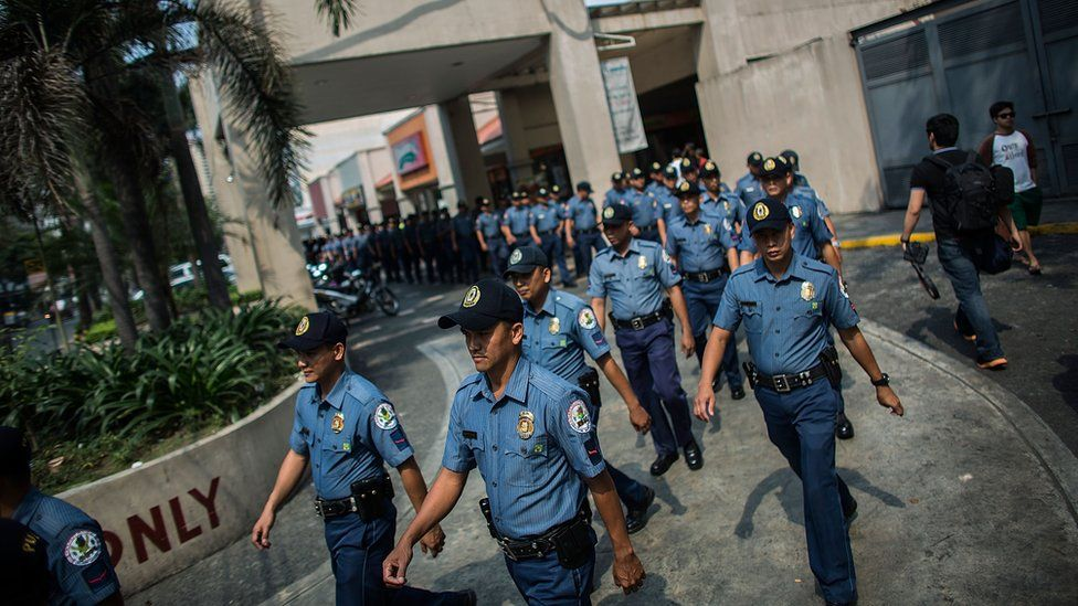 Dozens of police officers walk in file in Manila.