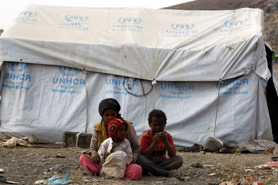 A group of children sit before a UN refugee agency tent