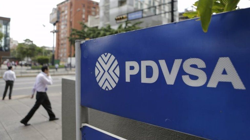 People walk past a sign with a PDVSA logo at its gas station in Caracas on 28 October, 2015.