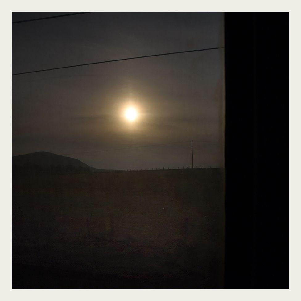 Evening sun is seen through the grubby window of a locomotive