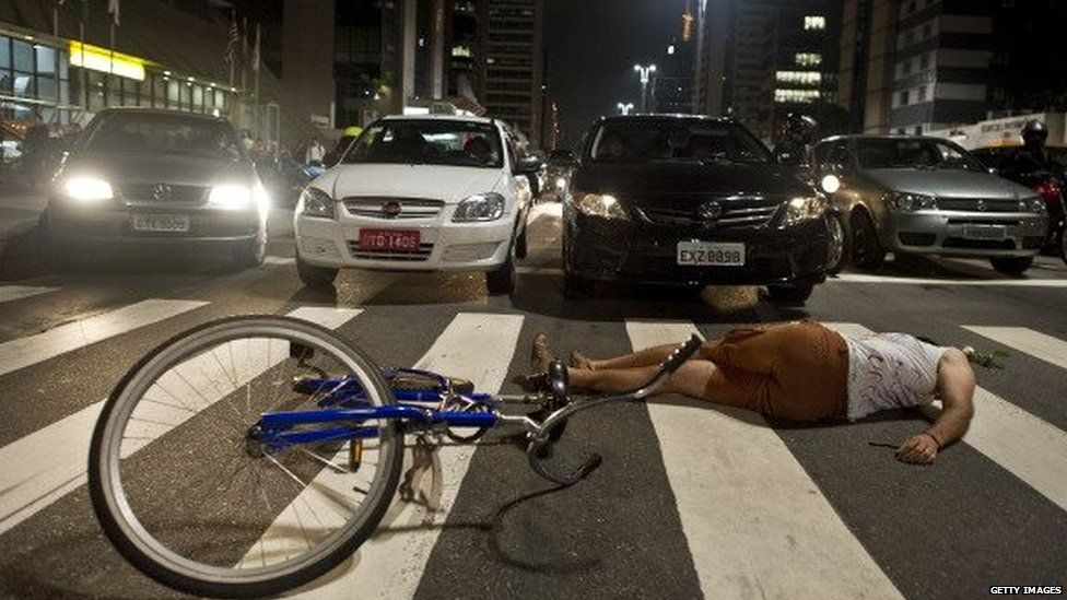 A cyclist lies on the ground on Avenida Paulista during a demonstration in Sao Paulo on 6 March, 2012