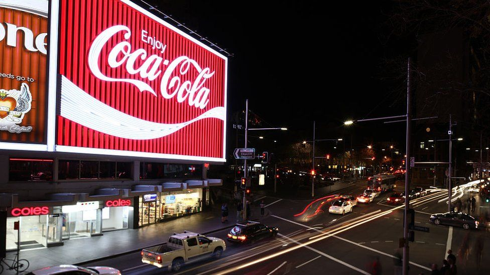 """A famous neon """"Coca-Cola"""" sign hangs over Sydney's Kings Cross suburb"""