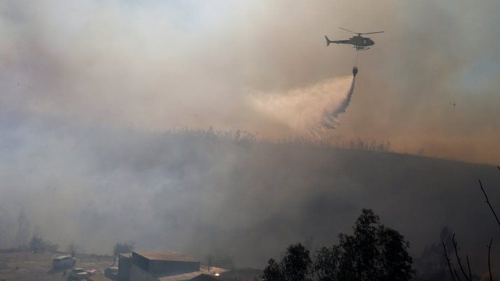 A helicopter drops water on a forest fire in Valparaíso, Chile. Photo: 24 December 2019