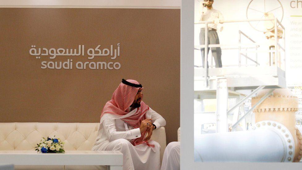 Man in Saudi dress by Saudi Aramco signage