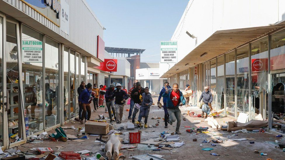 People flee from police as they carry goods while looting and vandalising the Lotsoho Mall in Katlehong township, East of Johannesburg, on July 12, 2021