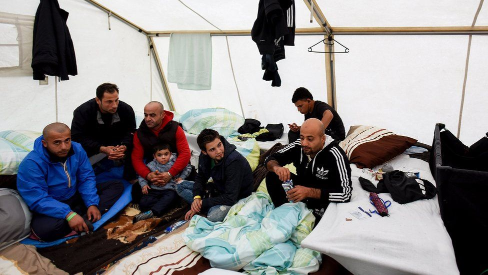 Migrants from Syria sit in their tent in a refugee camp in Celle, Lower Saxony, Germany (October 15, 2015)