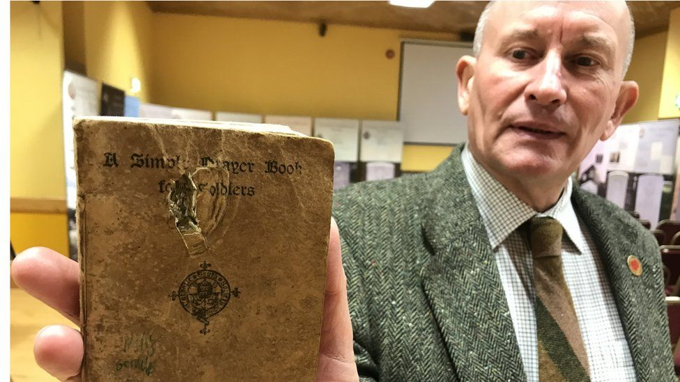 David Keys holds A Simple Prayer Book for Soldiers issued by the Catholic Truth Society which belonged to Private James Monaghan that has a hole made by the bullet that killed him