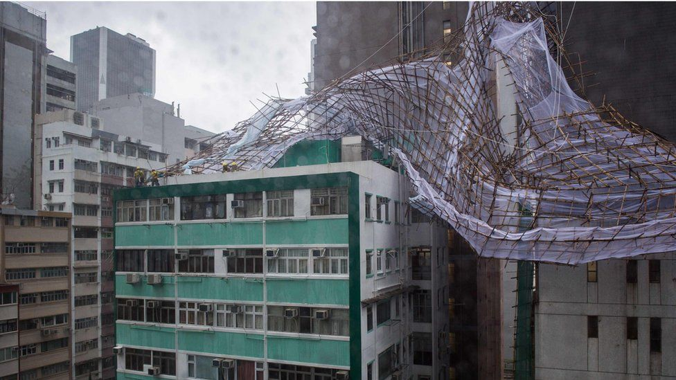 Rescue workers attempt to secure collapsed bamboo scaffolding on the top of a tall building in Hong Kong on 2 August 2016.
