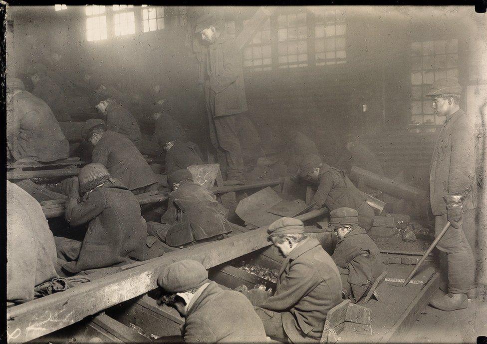Small boys breaking coal.